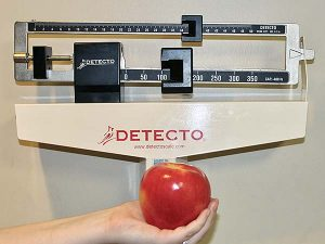 top of medical scale with hand holding red apple